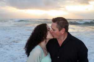 Couple kissing on the beach with the morning sun rising in background