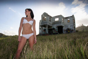 lingerie model in white two piece posing with abandoned house