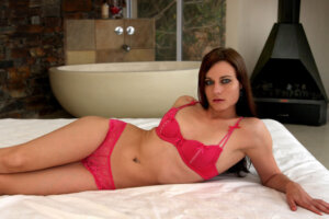 exquisite blue eyed brunette model in pink two piece lingerie on bed
