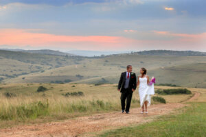 Bride and groom holding hands while walking at sunset