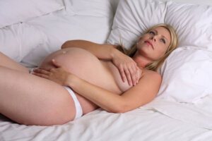 pregnant lady lying in bed on her back