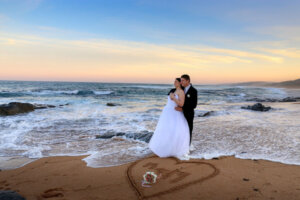 wedding couple posing at sunset on the beach with a heart drawn into the sand