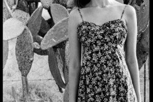 Model posing in sundress against prickly pear bush