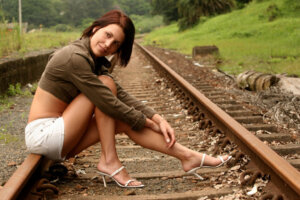 female model posing on railway line wearing white shorts and brown denim jacket