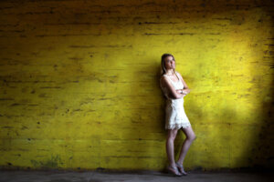 blond model in white dress posing against yellow wall