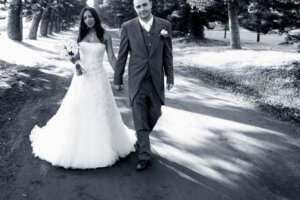 bride and groom holding hands walking down a tree lane