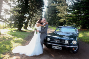 Bride and groom posing with a 1965 Ford Mustang