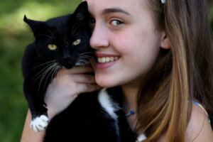 smiling teenage girl with flowers in her hair holding a black cat