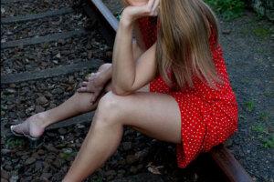 blond female model in red polka dot dress posing on railway line