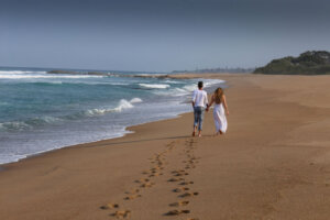 young couple walking along the beach holding hands