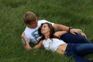romantic couple lying in each others arms in green grass