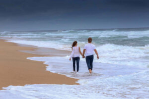 young couple holding hands walking along the beach