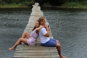 teenage couple sitting back to back on a bridge