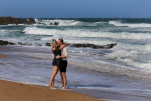 couple kissing on the beach with stormy ocean in background