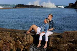loving couple sitting on a bridge with ocean in background
