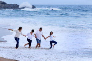 four family members running along the beach