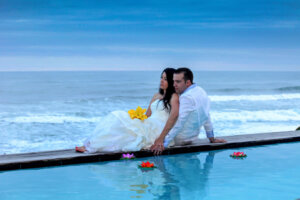 wedding couple posing next to a swimming pool with the ocean in the background