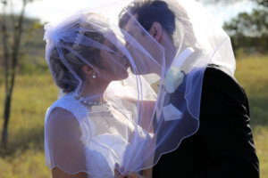 wedding couple kissing with wedding dress veil covering them