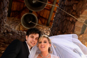 just married wedding couple posing with church bells