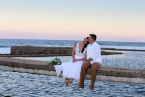 Bridal couple posing on a bridge with the ocean in the background