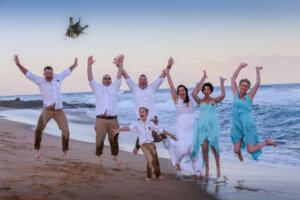 bridal party jumping doing a group jump on the beach