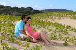 couple sitting on the sand amongst dunes