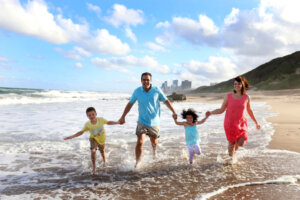 couple and children running through water during family photography session