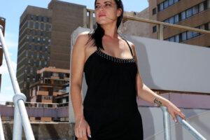 fashion model wearing black dress in urban cityscape