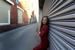 photographic model posing in red dress in city alleyway