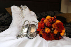 bridal shoes and wedding bouquet placed on top of wedding dress