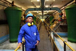 industrial worker with blue coveralls standing at underground pump station