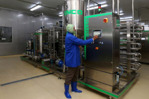 worker with industrial food pasteurization machine