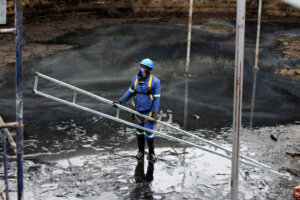 worker with protective clothing at bottom of empty toxic waste holding tank