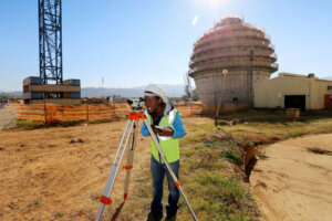 land surveyor taking a reading at industrial construction site