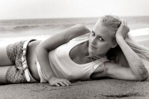 female model in white top lying on the beach