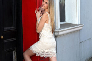 blond model in white dress posing in red and black door arch