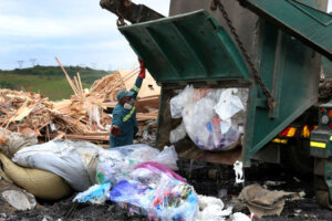 truck unloading waste at industrial waste site with worker looking on