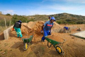 black worker pushing a wheelbarrow full of building sand